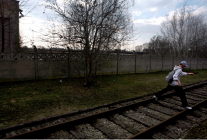 A boy jumps over the railway tracks connecting Auschwitz and Birkenau on his way to school