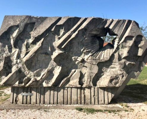 A large stone monument, depicting a line of soldiers in full charge. This piece perfectly reflects the style of rough stone texture, which recalls ancient art carvings.