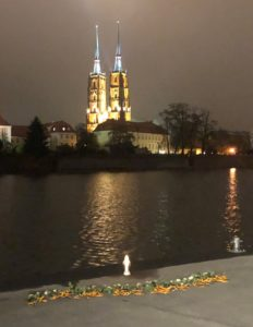 At the Remembrance Ceremony, white roses were laid on the bank of the Oder River, around a small, white lantern. The scene overlooks Cathedral Island.