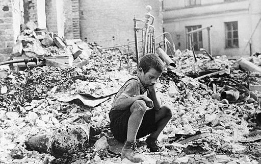"Polish boy in the ruins of the Warsaw, September 1939. Source, Julien Bryan captioned the photo in 1958: ""A BOY'S WEARINESS--Ryszard Pajewski was a study in dejection when I saw him sitting on a pile of rubble. Only nine, he had suddenly been made the family breadwinner - and there was no bread to be had"""