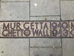 Markers of the former Warsaw Ghetto wall can be found throughout the city