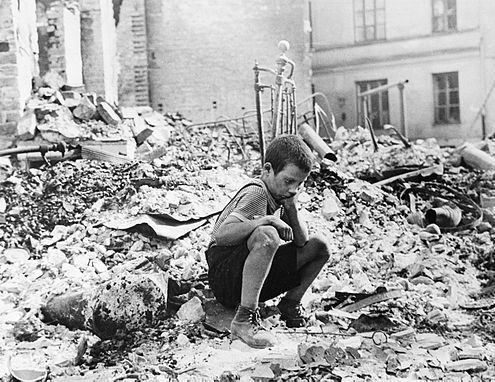 """Polish boy in the ruins of the Warsaw, September 1939. Source, Julien Bryan captioned the photo in 1958: """"A BOY'S WEARINESS--Ryszard Pajewski was a study in dejection when I saw him sitting on a pile of rubble. Only nine, he had suddenly been made the family breadwinner - and there was no bread to be had"""""""
