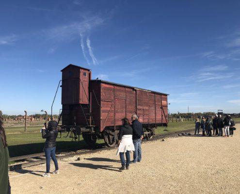 An old train car sitting on the tracks in Birkenau